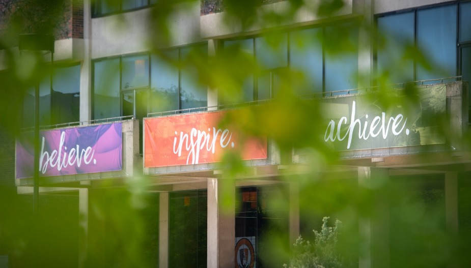 """Trees in front of building with banners that say """"Believe, Inspire, Achieve."""""""