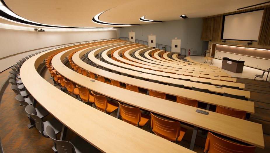 Large lecture hall with grey and orange chairs behind large tables.