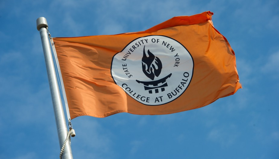 Orange flag with Buffalo State crest against blue skies.